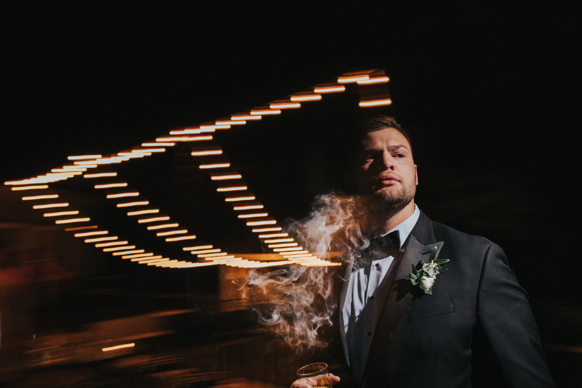 A groom smokes a cigar during the reception under the lights