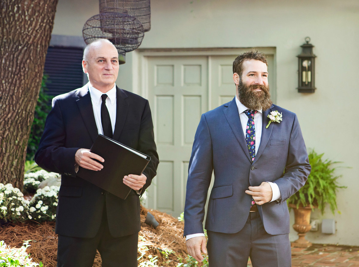 NOLA groom waits for his bride with wedding officiant in the Terrell House coutyard