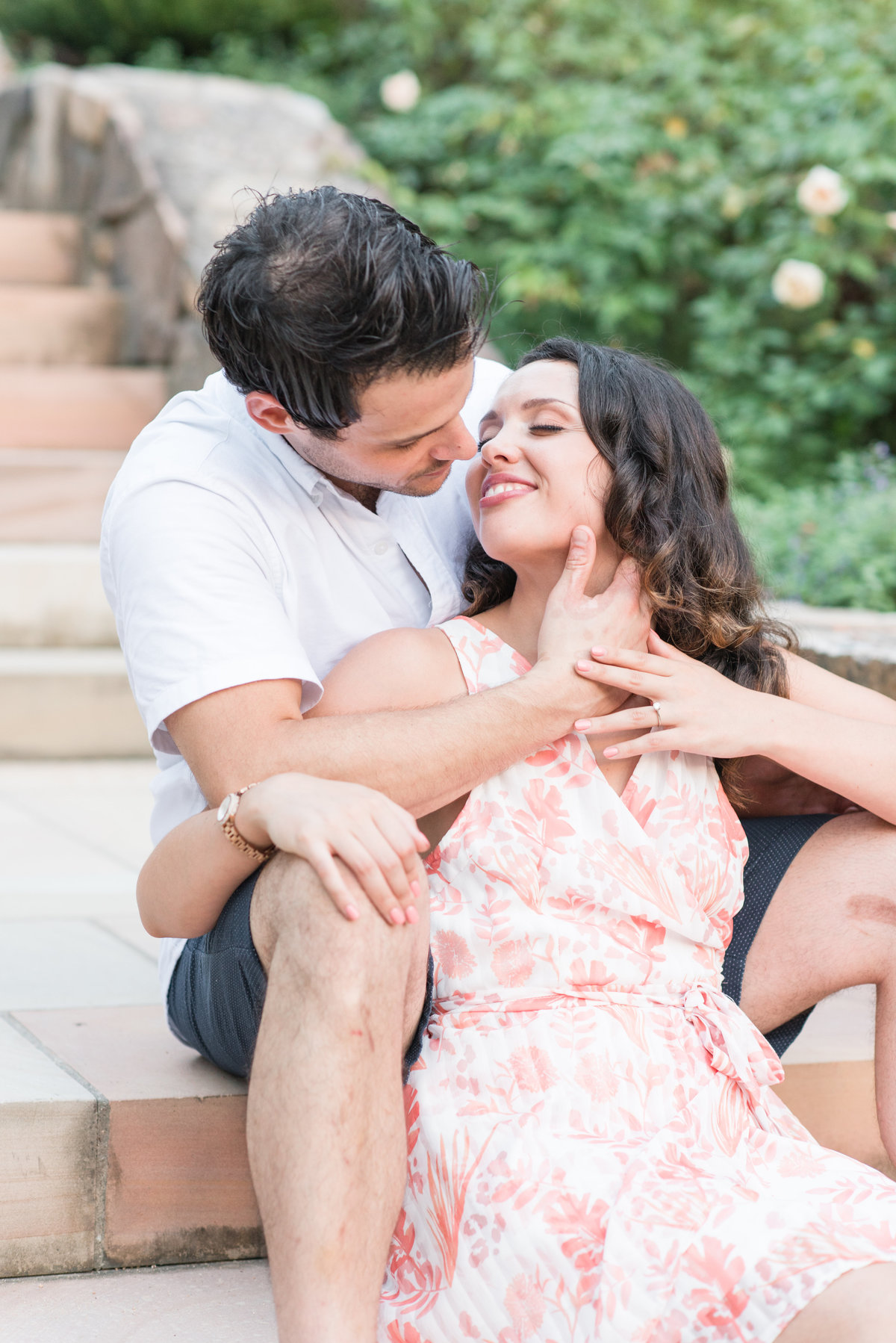 an engagement session at Sarah P Duke Gardens with a bride sitting on the marbled steps snuggled into her fiance almost about to kiss each other in front of a rose garden in Durham