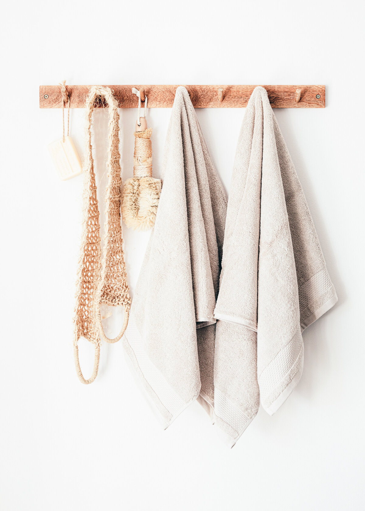 A flannel and loofah hang from a wooden rack against a white wall.