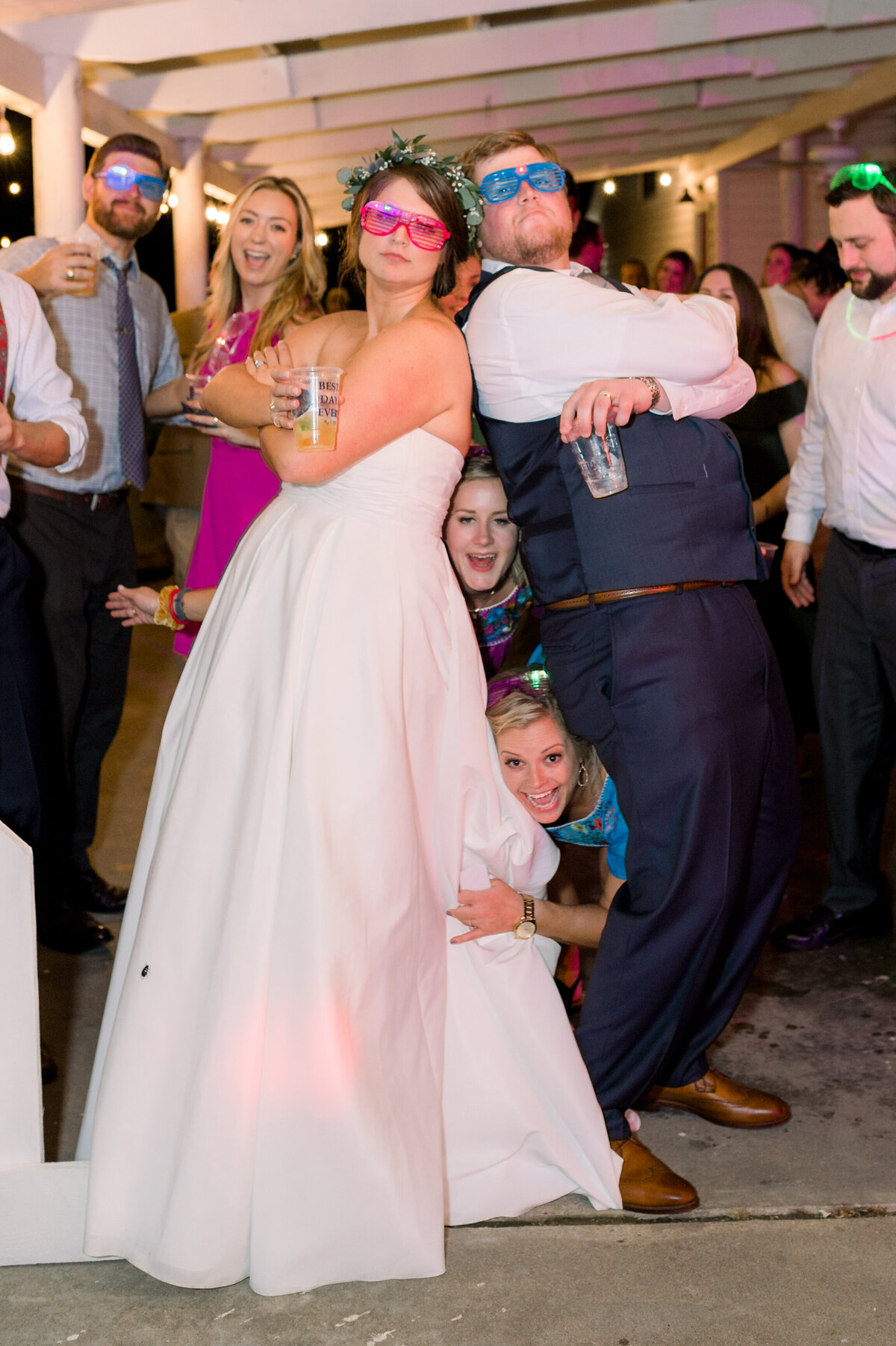 A fun reception photo of the bride and groom wearing silly glasses and posing back to back