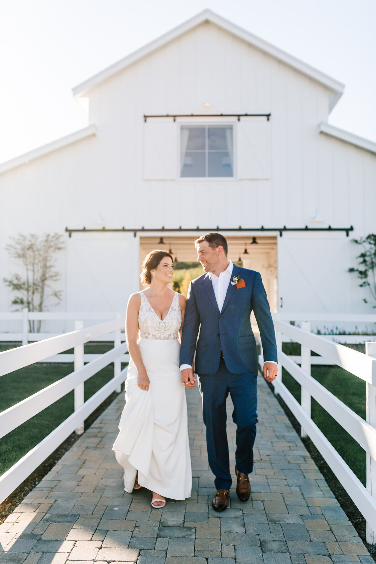 Bride and groom walking in front of white barn at sunset during Harmony Meadows wedding