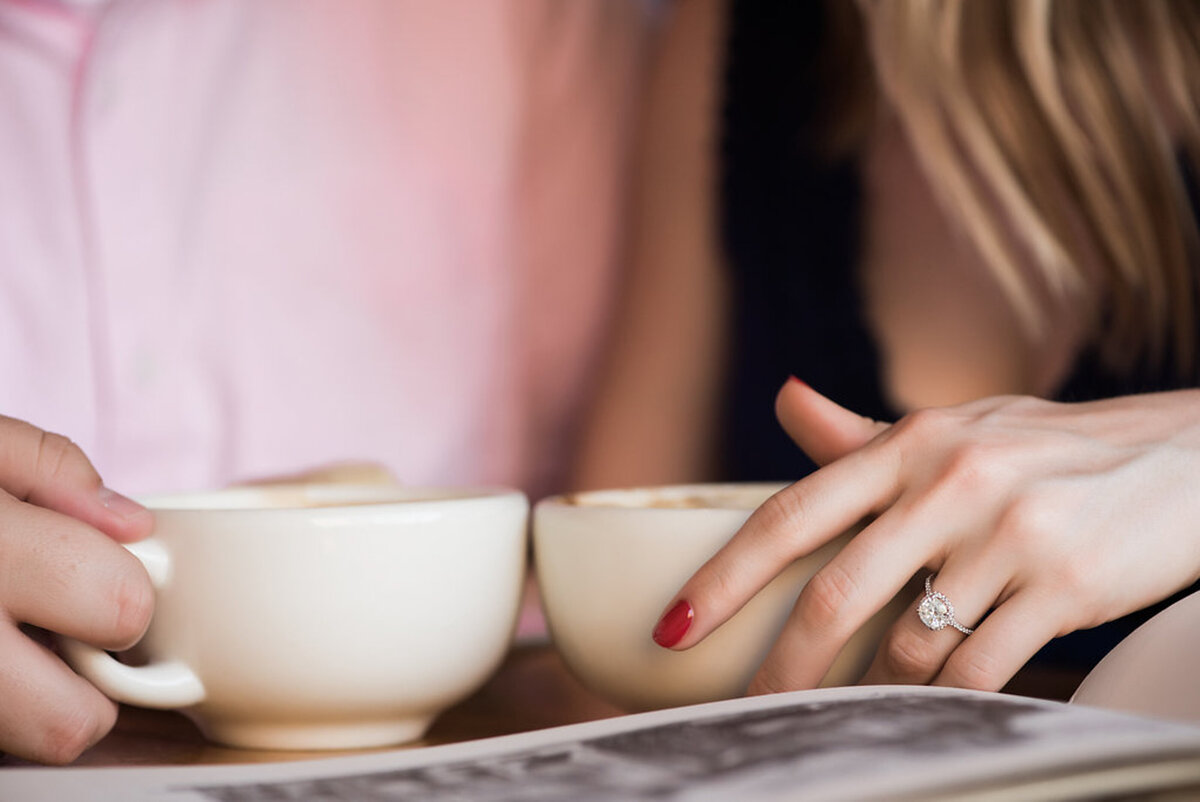 Coffee cup and rings at coffee shop engagement session