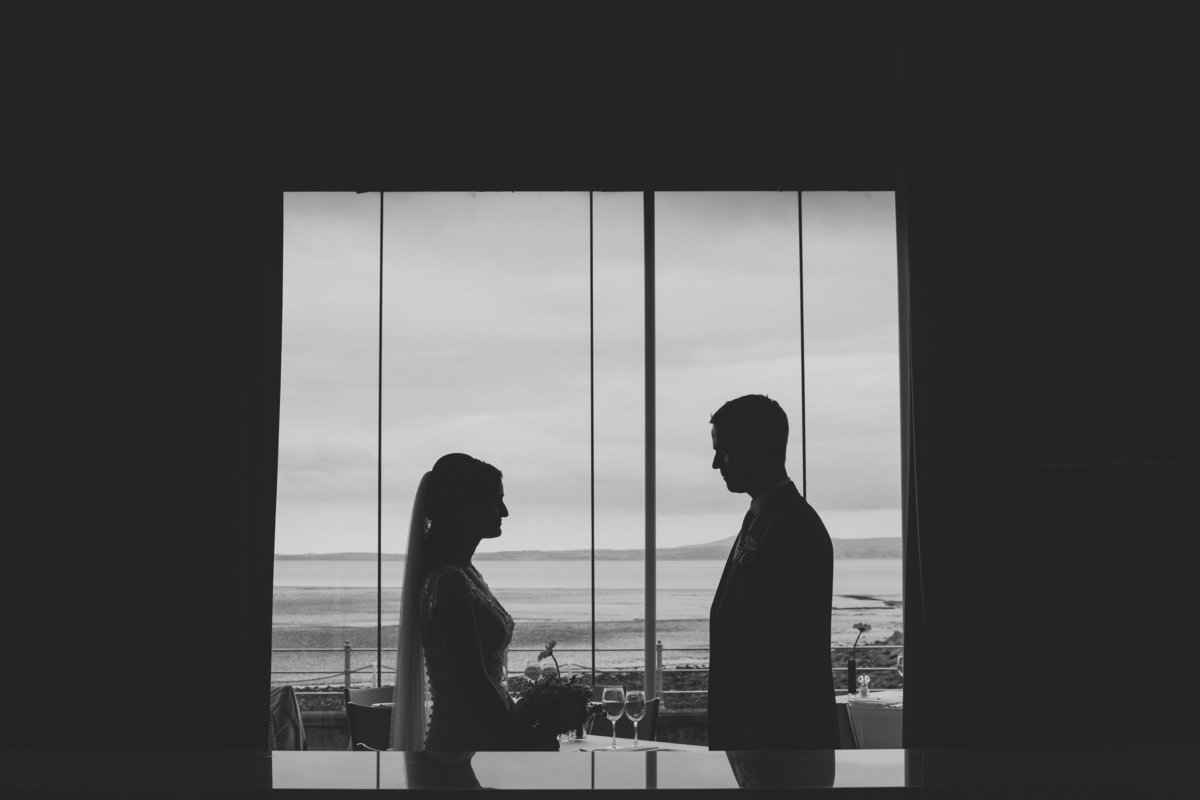 silhouette of bride and groom in window