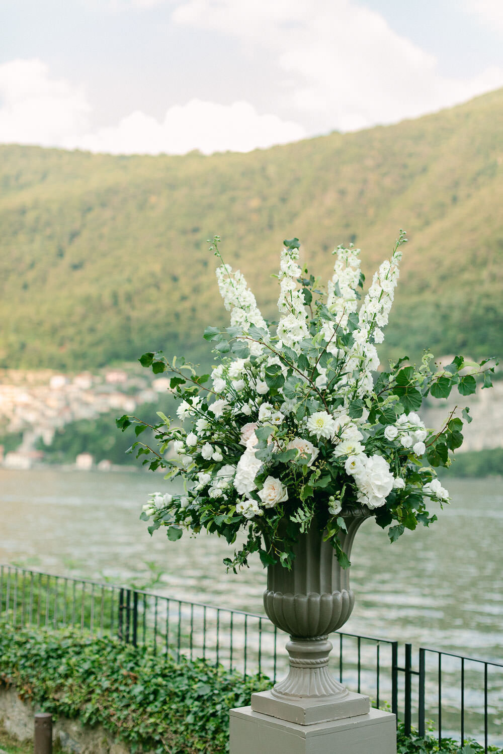 White and green floral arrangement in front of lake como italy wedding ceremony