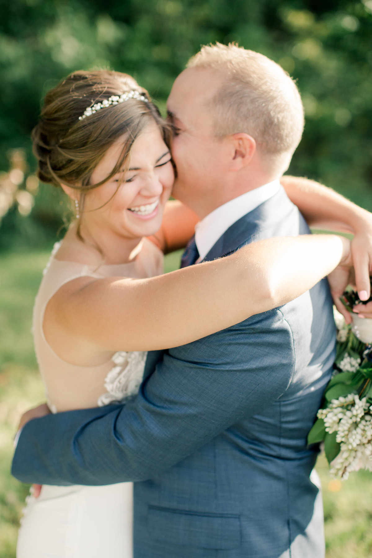 groom kisses brides cheek in wedding portraits outside
