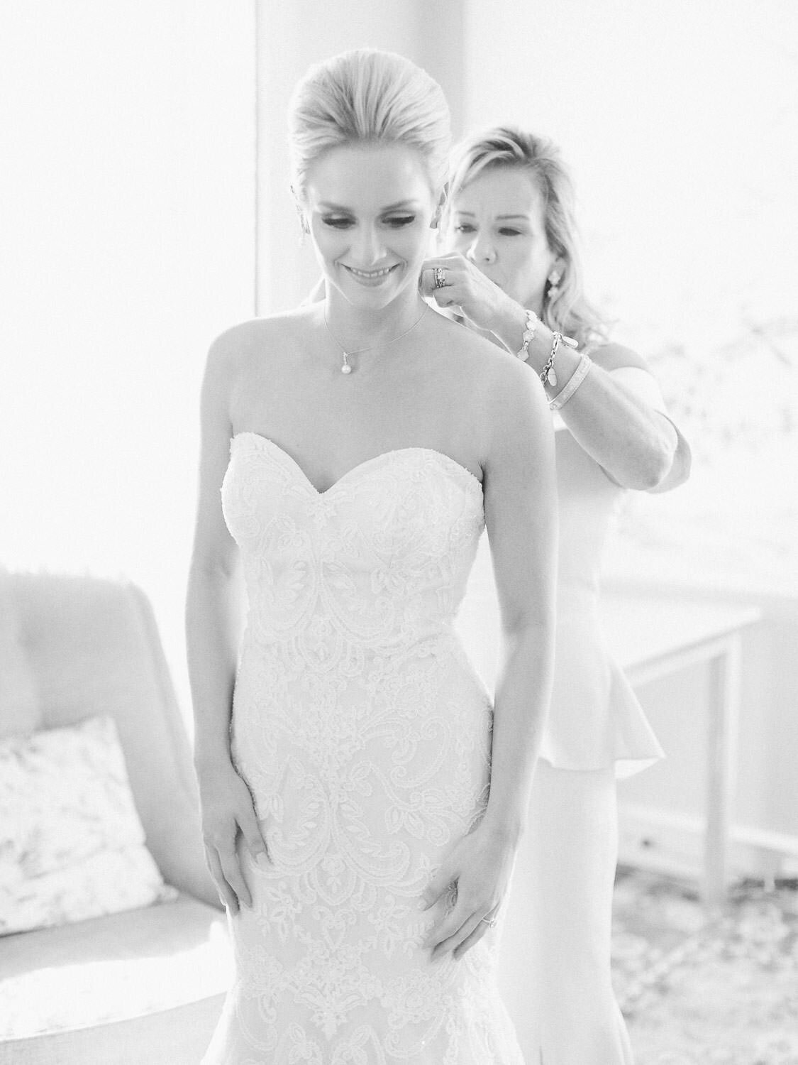 Mother helping bride put on necklace black and white