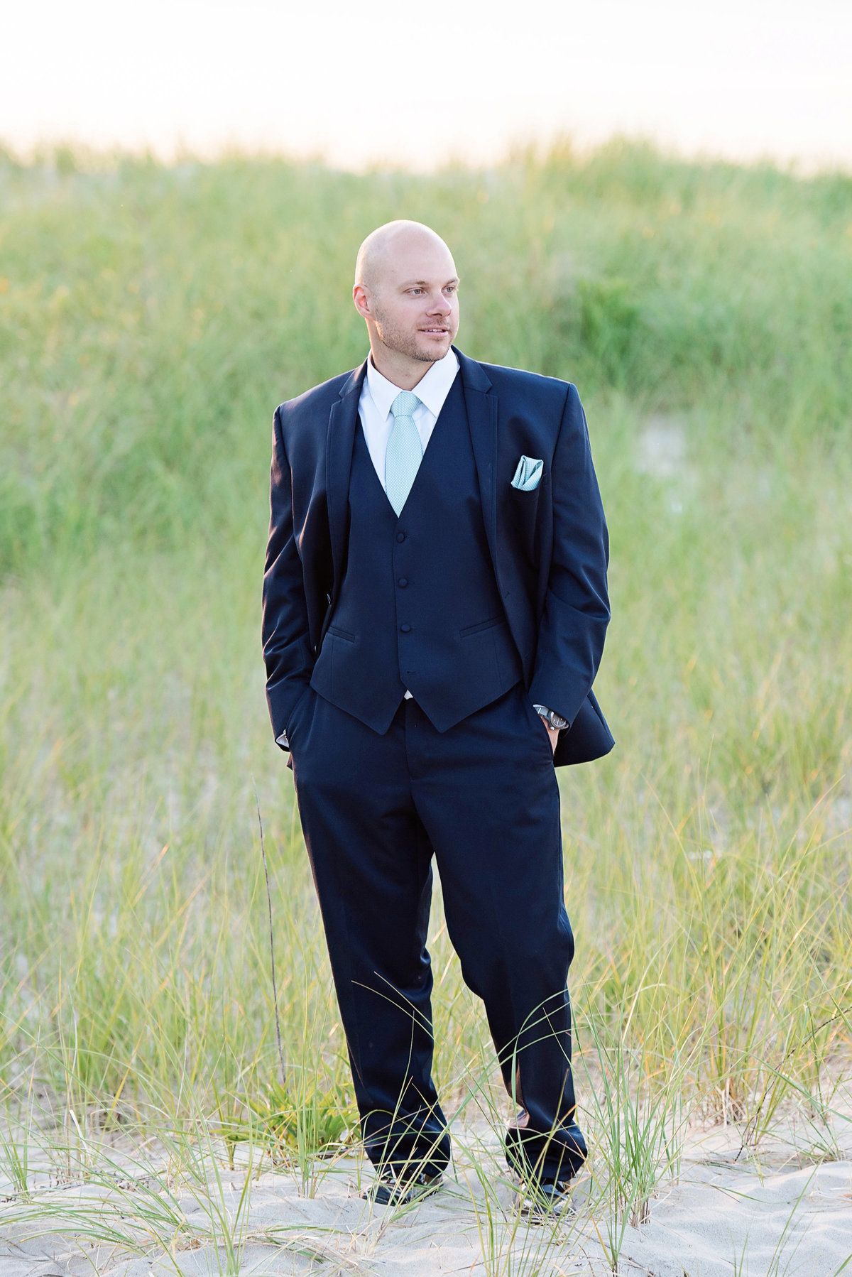 solo shot of groom with his hands in his pockets on the beach from wedding at Pavilion at Sunken Meadow