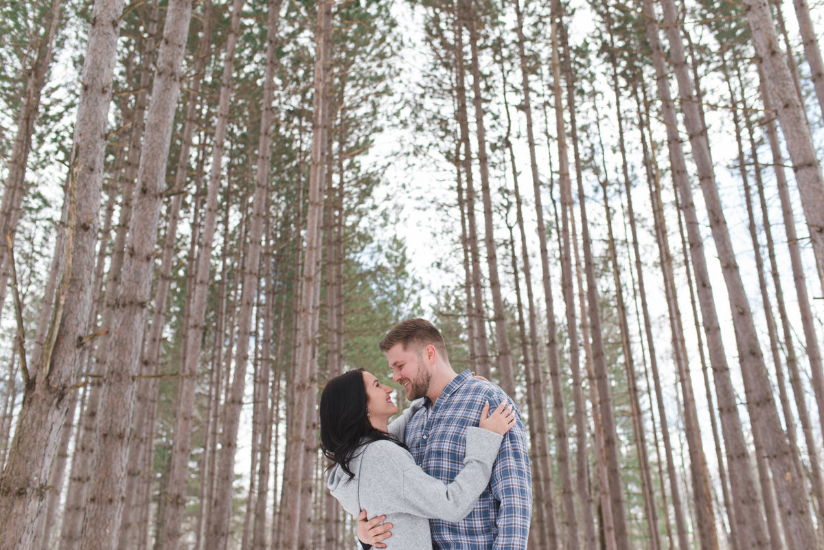 engaged couple standing together among tall pine trees