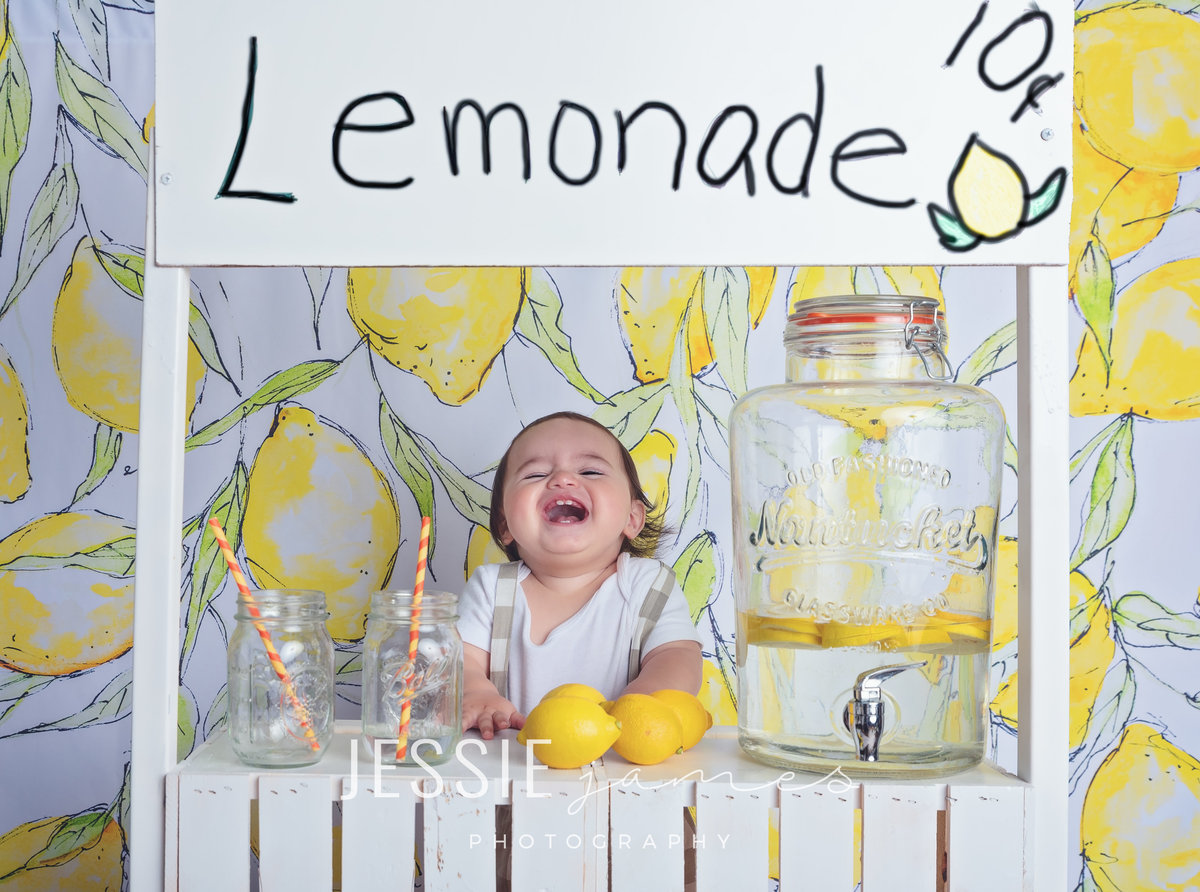 baby girl laughing behind a mini lemonade stand  for photography session