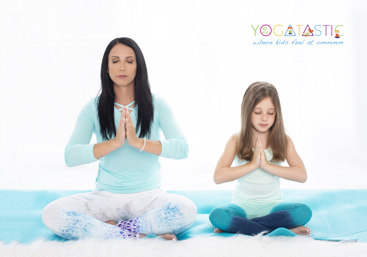 personal branding photography for  yoga  instructor  with a child  teaching her  how to do yoga sitting on matt with folded hands and  long hair