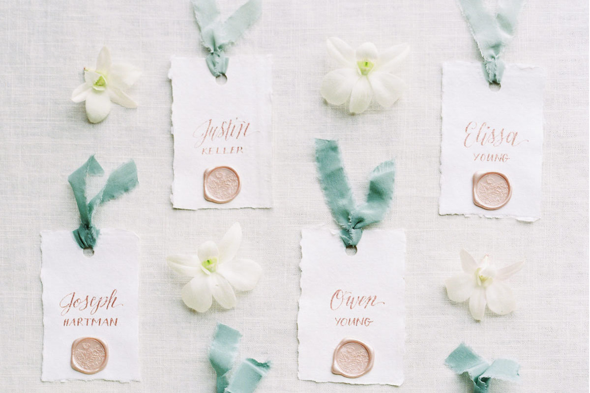 handmade paper escort cards with silk ribbon and champagne wax seal