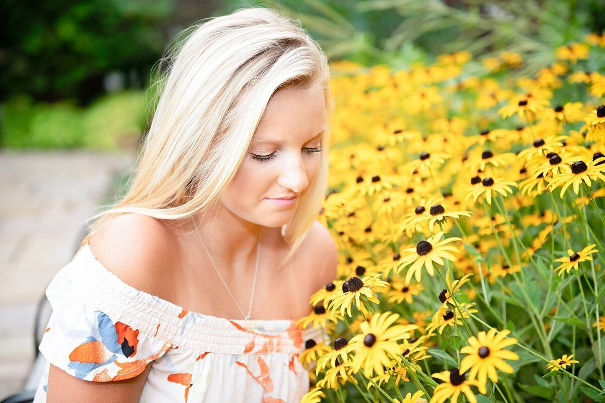 High school senior girl in floral off-shoulder dress crouching among Black-eyed Susan flowers during her senior session at Mellon Park in Pittsburgh, PA