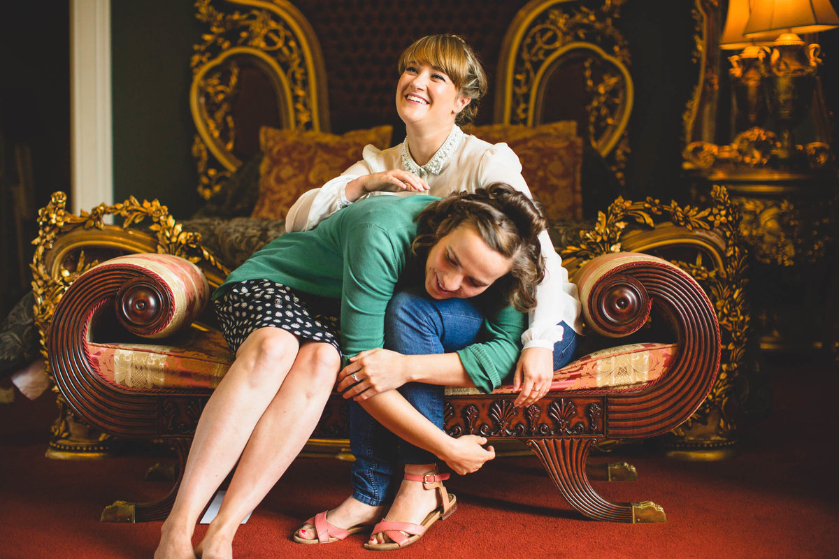 bridesmaids laughing in a gold room at allerton castle