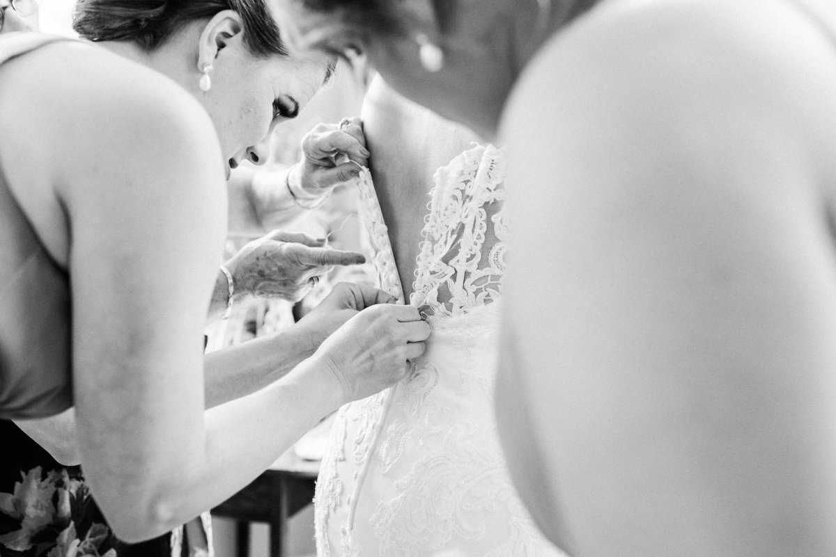Black and white photo of bridesmaids zipping and buttoning up a wedding dress