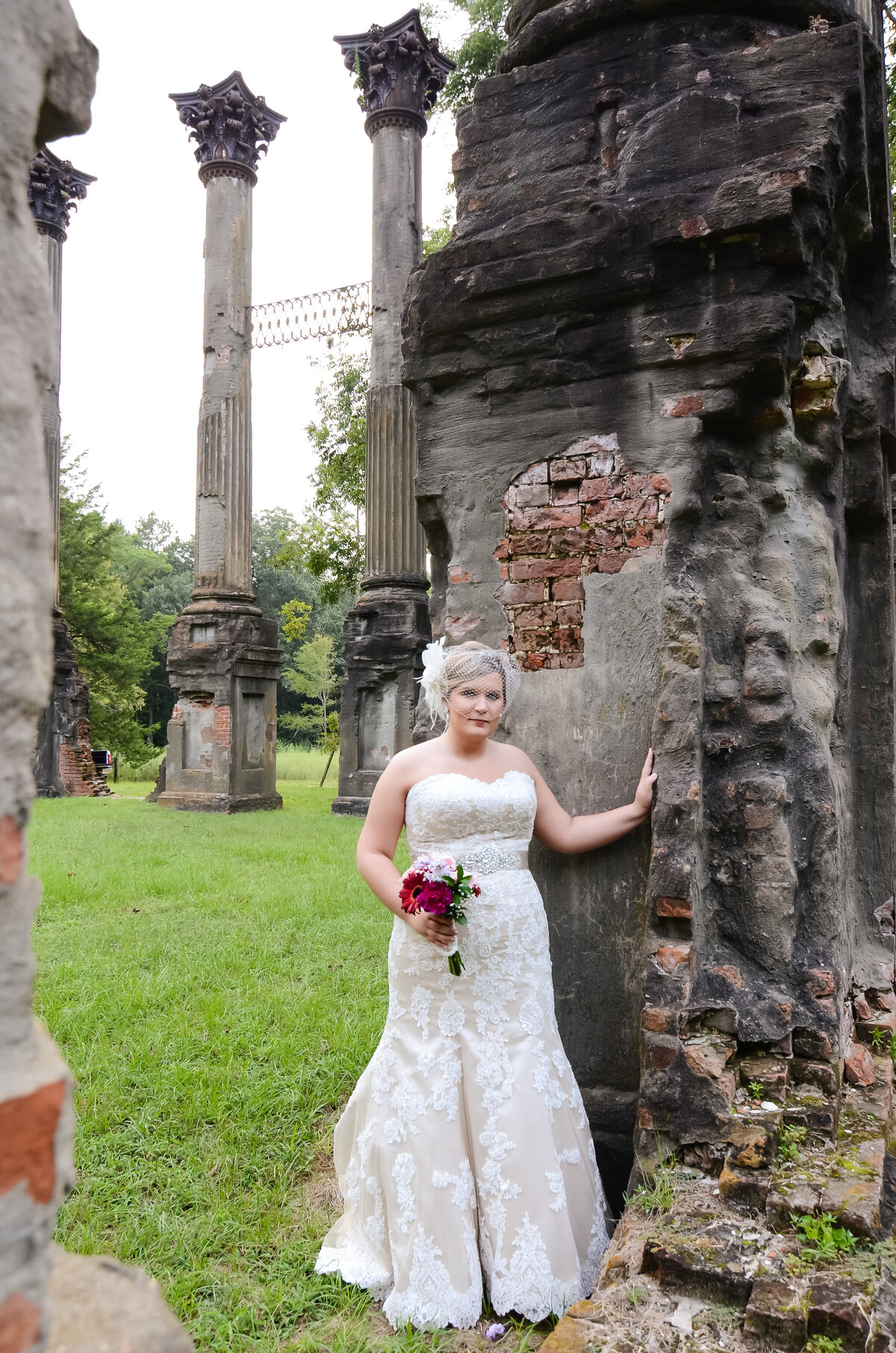 Beautiful bridal portrait photography: Bride with a birdcage veil stands among the ruins at Windsor plantation in MS