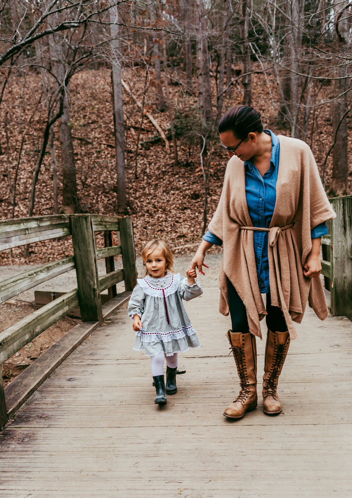 Mother and daughter walking across a wooden bridge holding hands