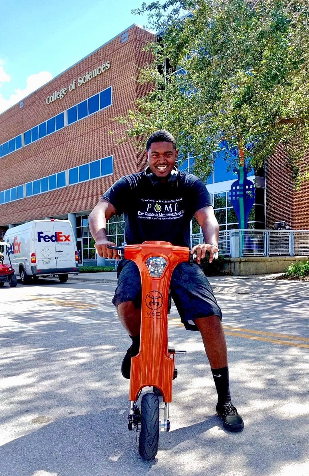College student riding on campus on a Bronze Go-Bike M1