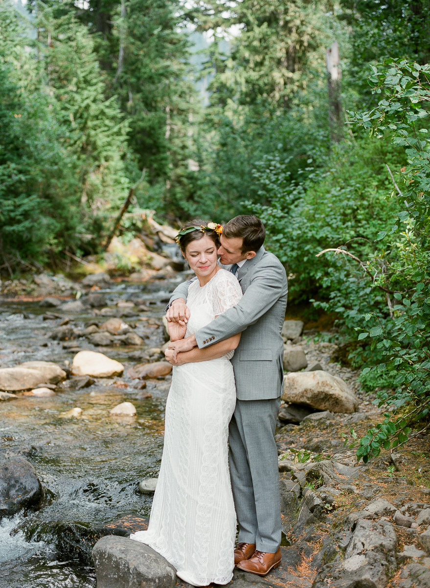 wedding couple stands on rock in the middle of fall mountain stream washington mt rainier