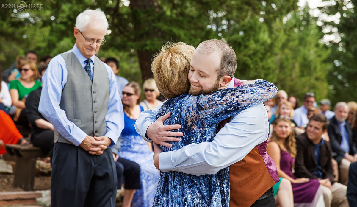Groom hugs mom at outdoor wedding ceremony at Colorado Mountain Ranch in Boulder