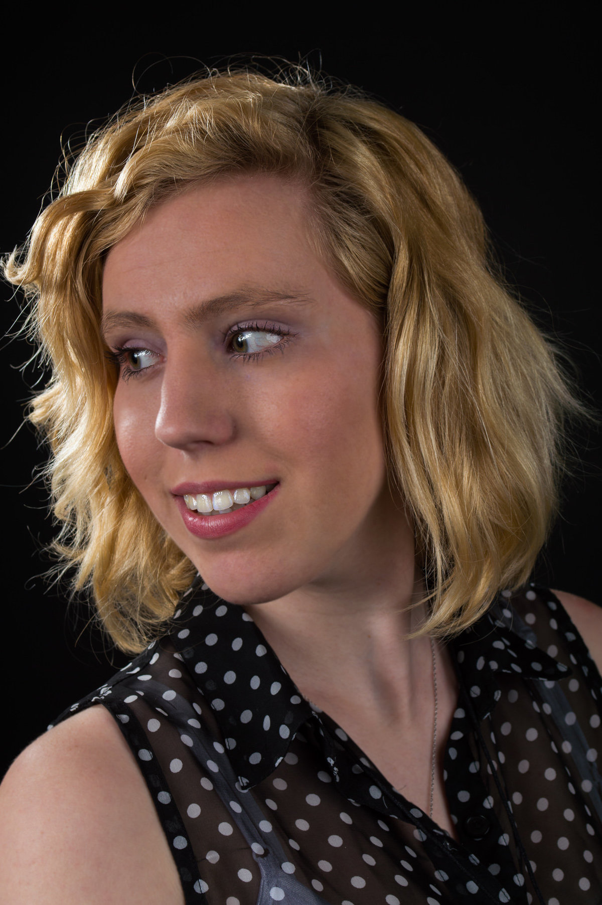 Portfolio headshot of a young adult with a black background