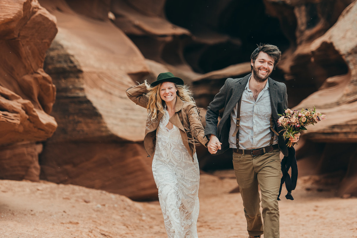 Photo of happy couple runs through Arizona slot canyon for adventure wedding