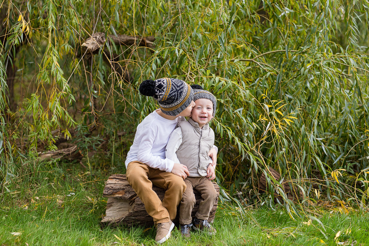 Older brother kissing younger brother on cheek outdoors {Oakville Child Photographer}