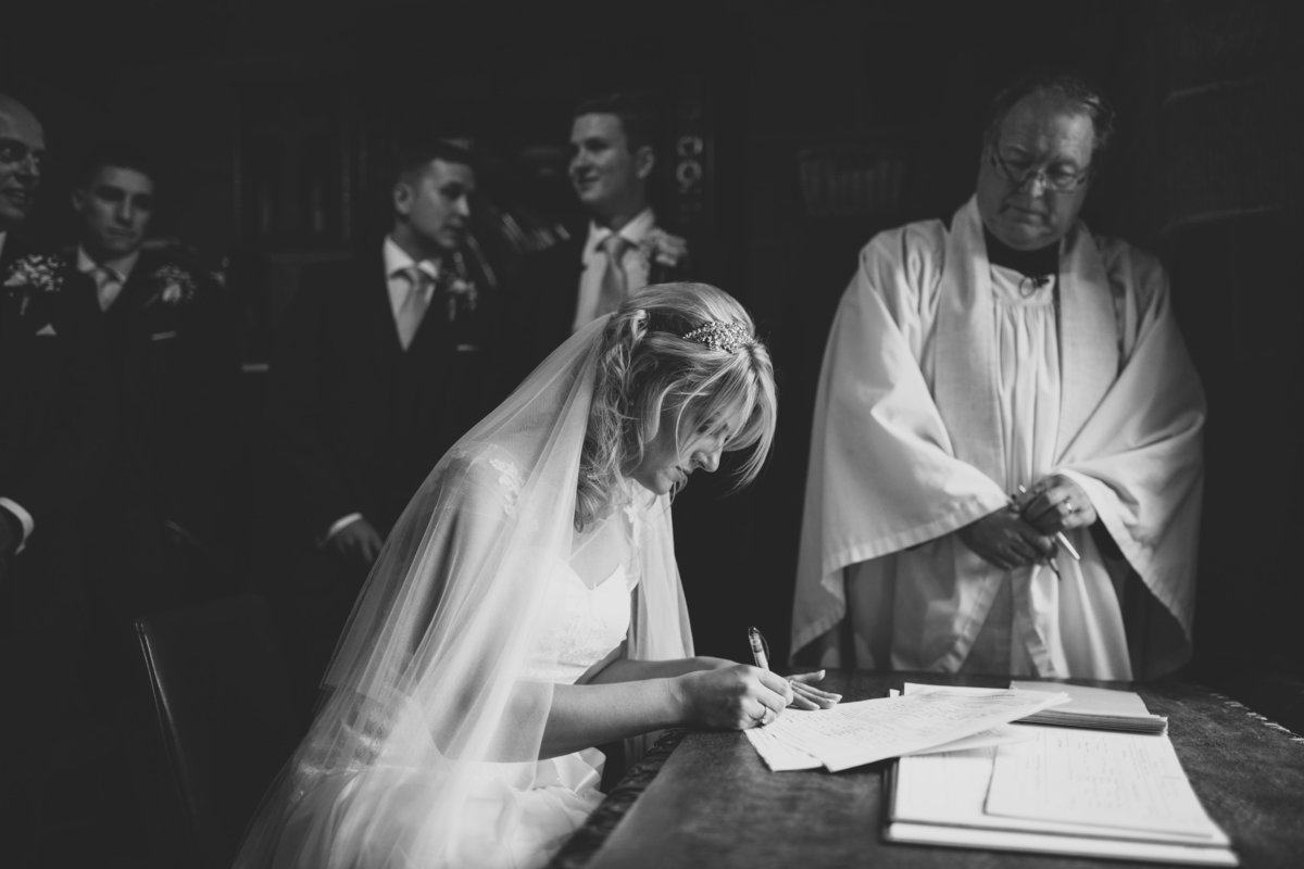 bride signing the register in b&w