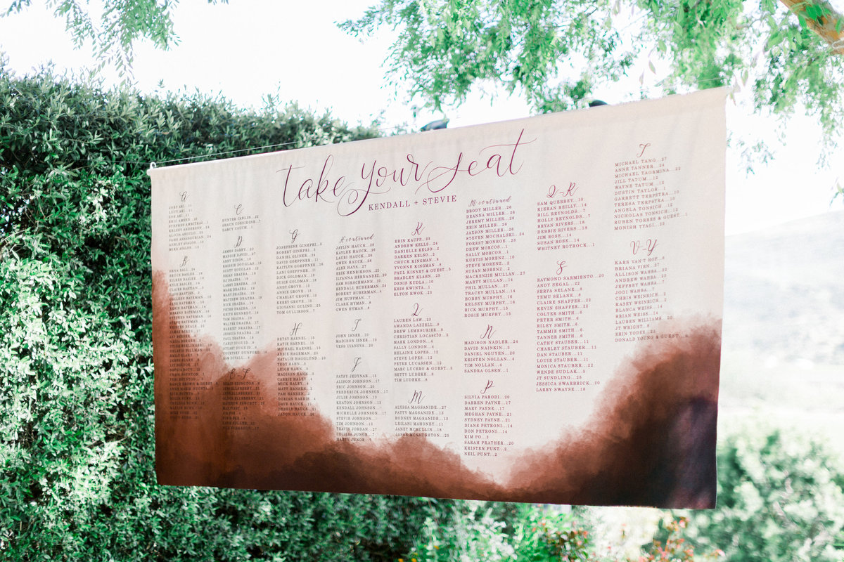 Pink hanging velvet seating chart at wedding reception at Maravilla Gardens