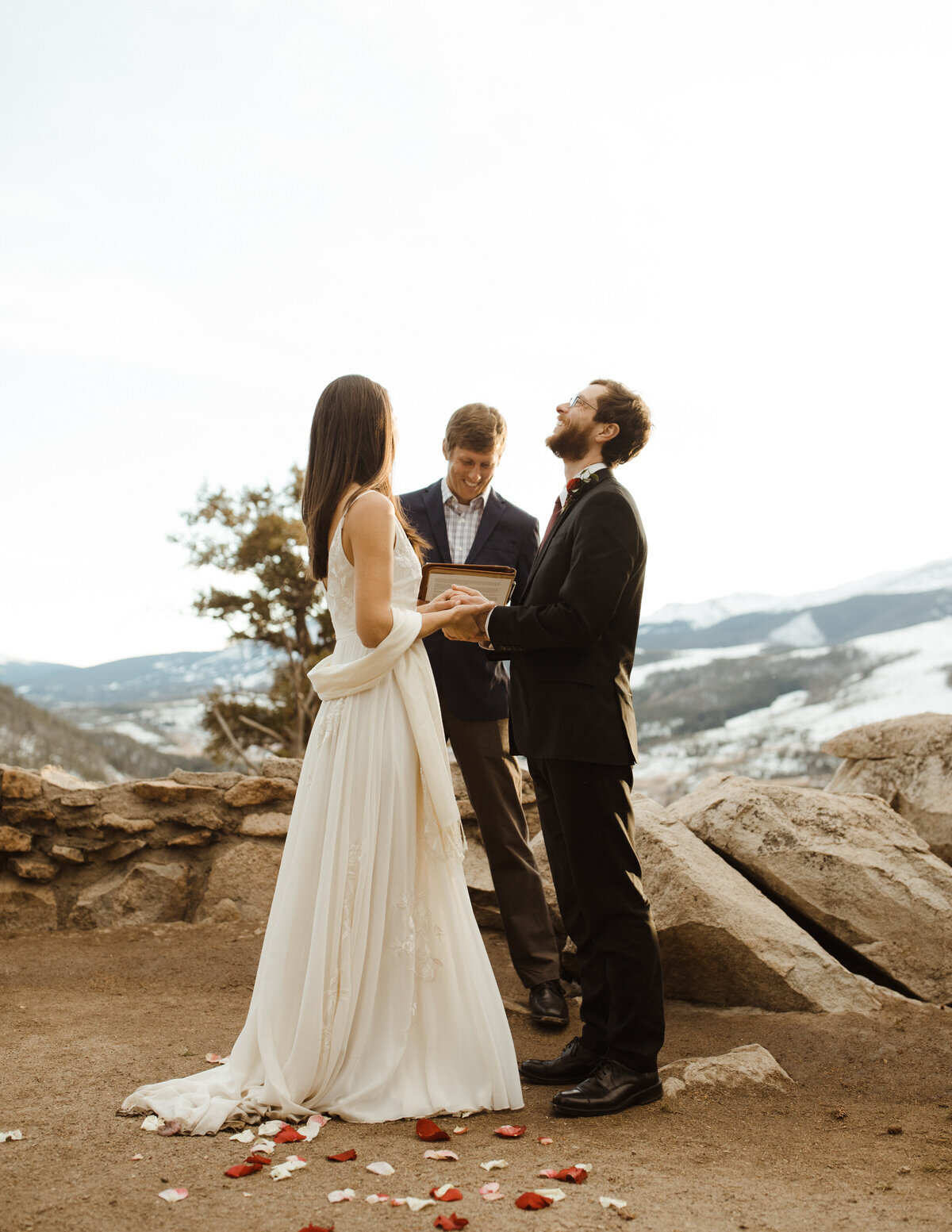 A bride and groom to be holds hands while their wedding happens, with a mountain in the background. There are rose petals on the ground and the groom is laughing, looking upwards