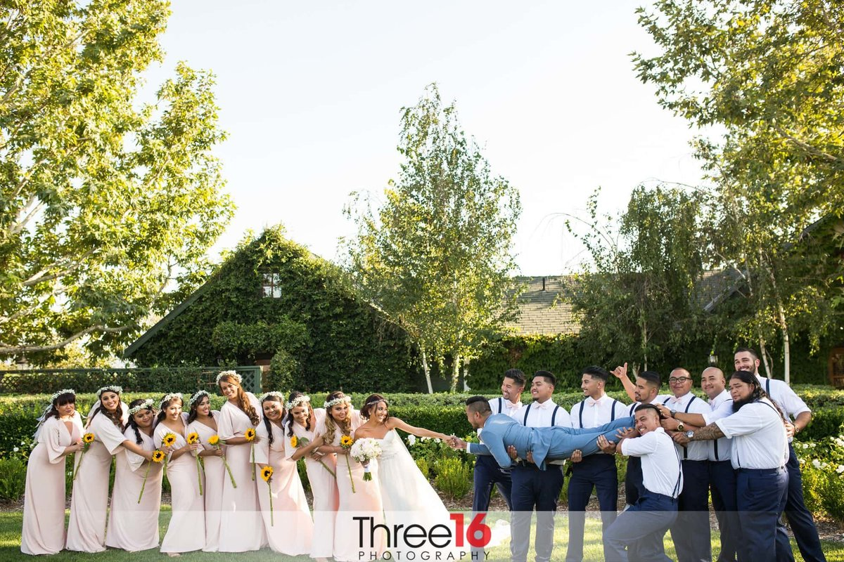 Fun photo of bridal party playing tug of war with the Bride and Groom