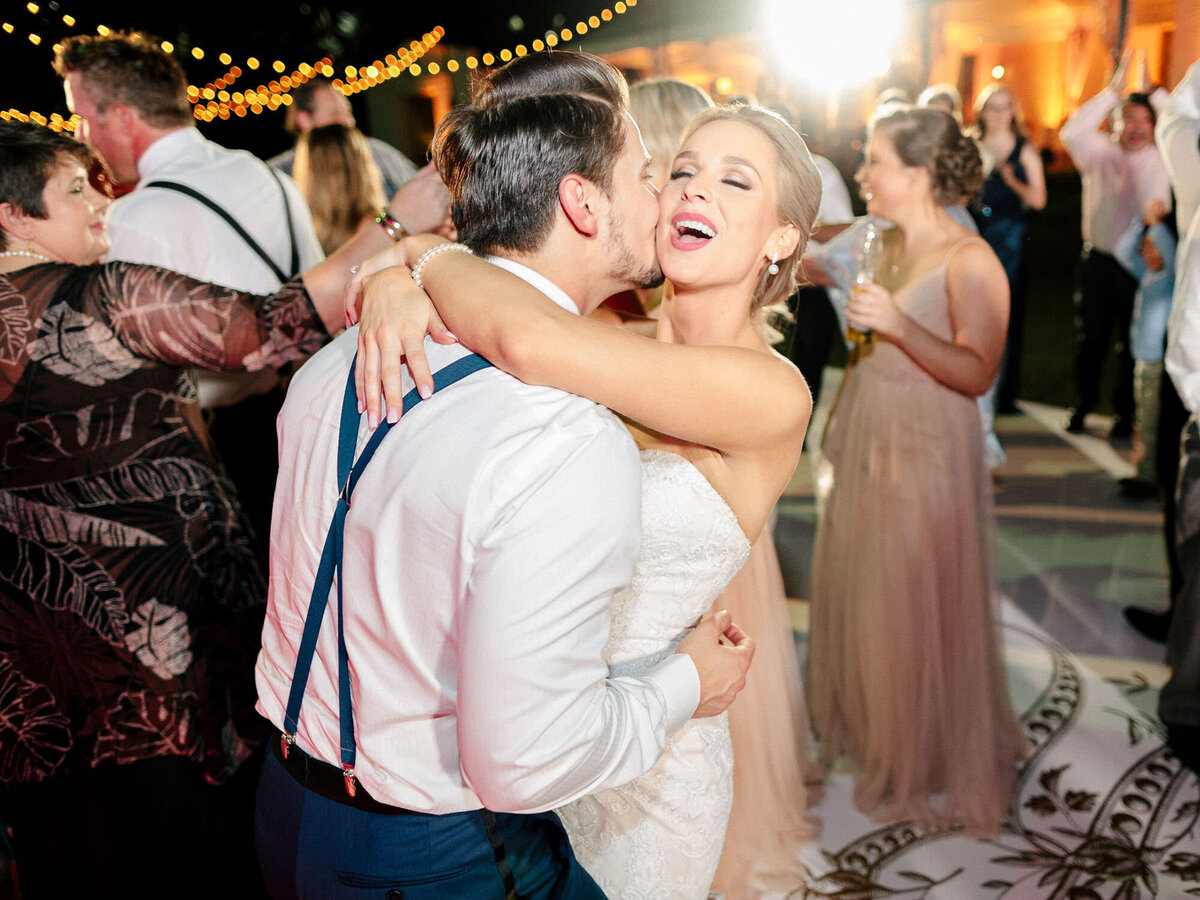 Bride and groom laughing and dancing at wedding reception outdoors