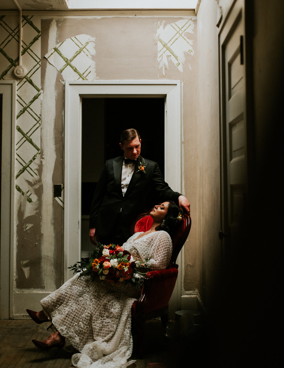 A bride sits in a lush red chair as her groom stands next to her with her bouquet from Gardenview Flowers