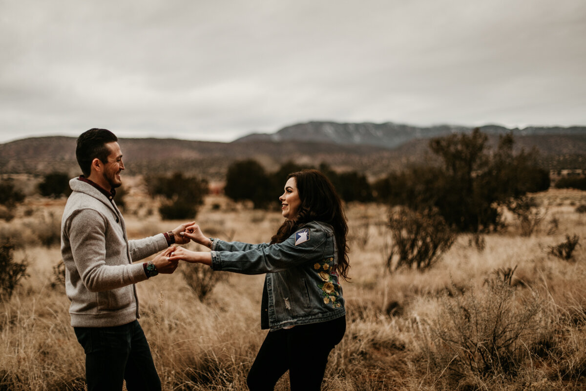 engaged couple dancing in the desert