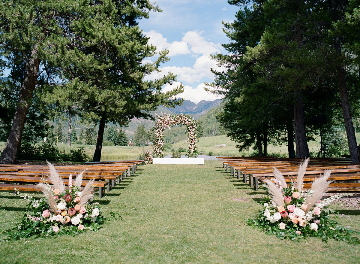 Empty outdoor wedding ceremony with wooden benches, two large flower arangements at the front, and a large flower arch at the end