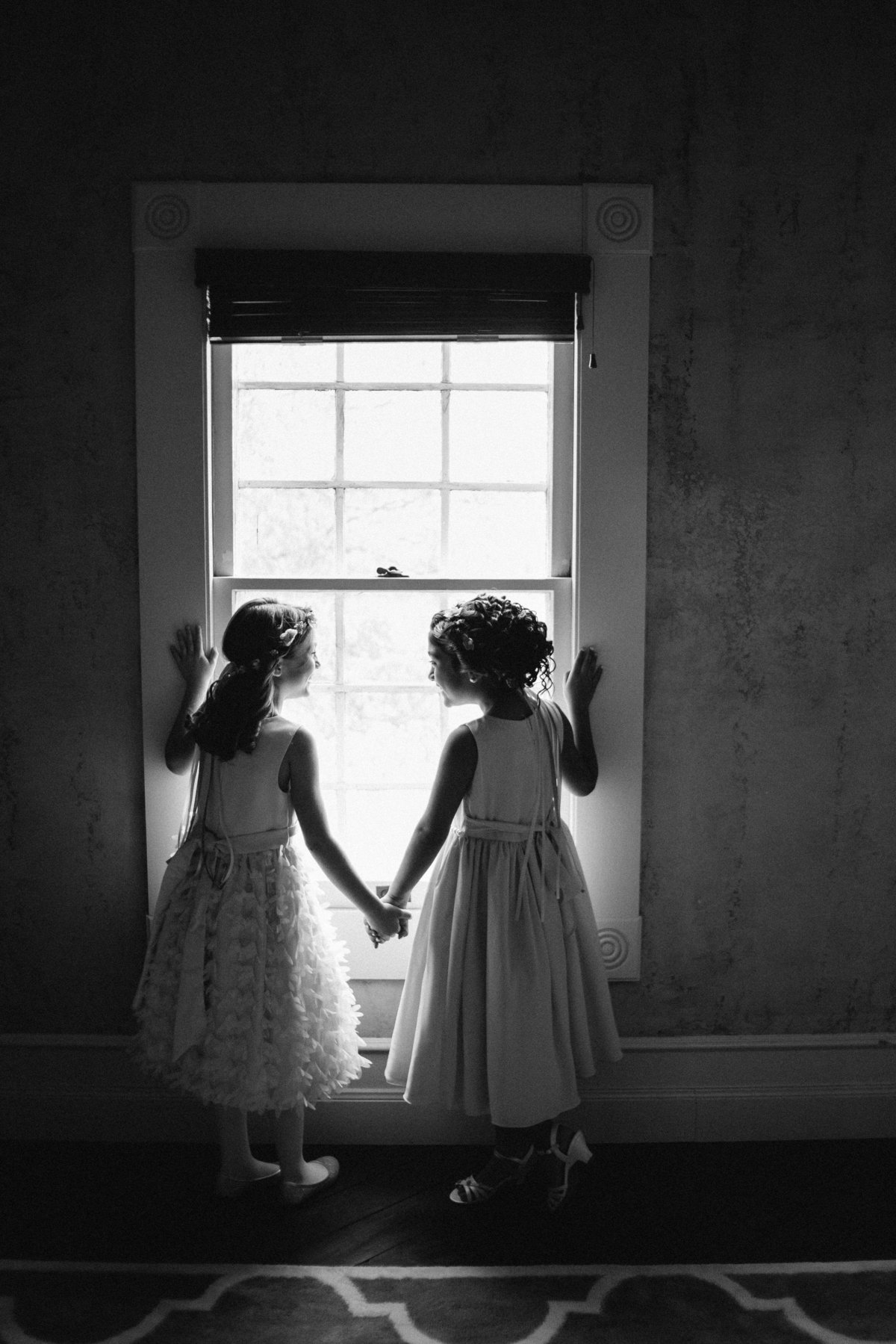 flower girls holding hands and looking out window while getting ready before ceremony at The Grande Hall at Hoffman Ranch