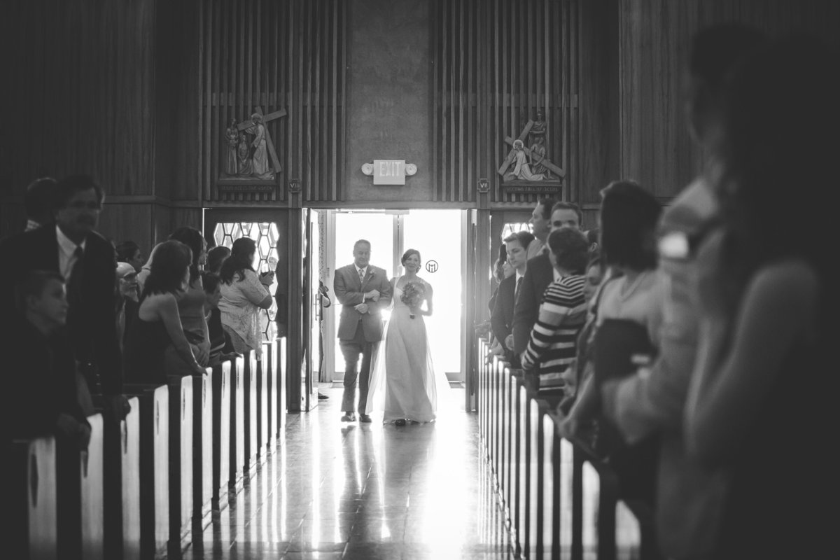 black and white photo of father walking his daughter down aisle for her wedding at Oblate School of Theology in San Antonio
