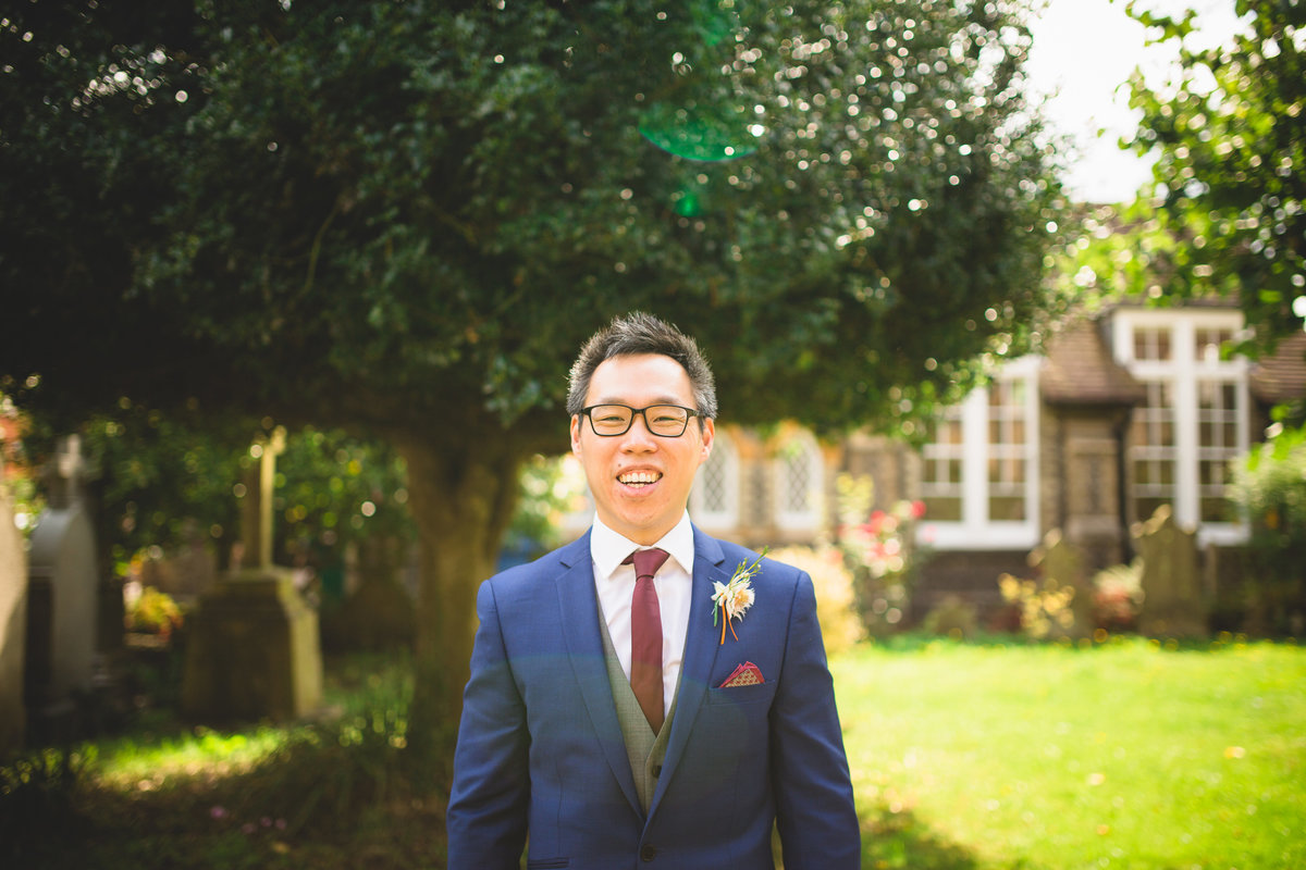 groom in wearing a blue suit in the church grounds laughing. photo has lens flare