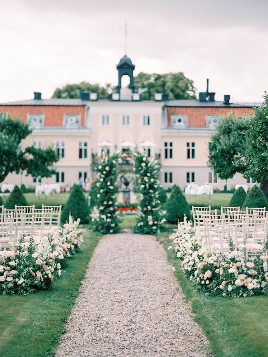 outdoor castle wedding ceremony with blush flower arrangements