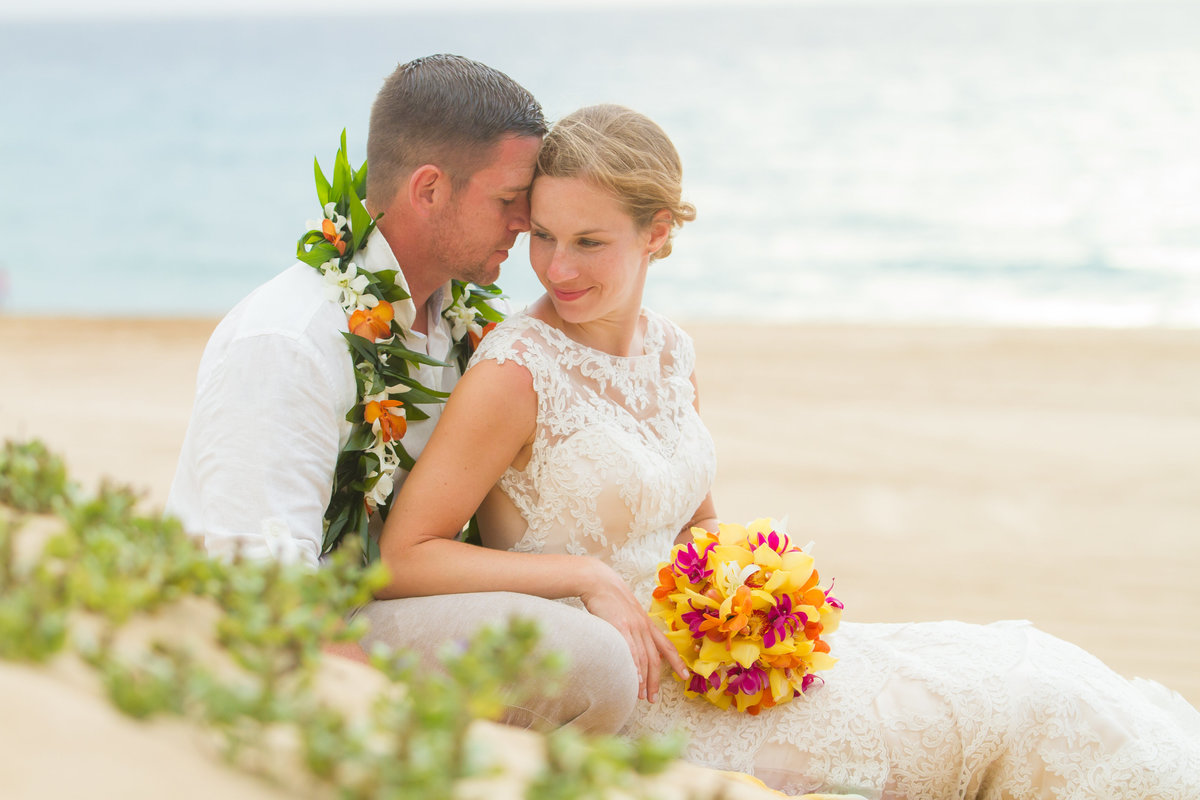 Intimate moments during Kauai beach wedding elopement.