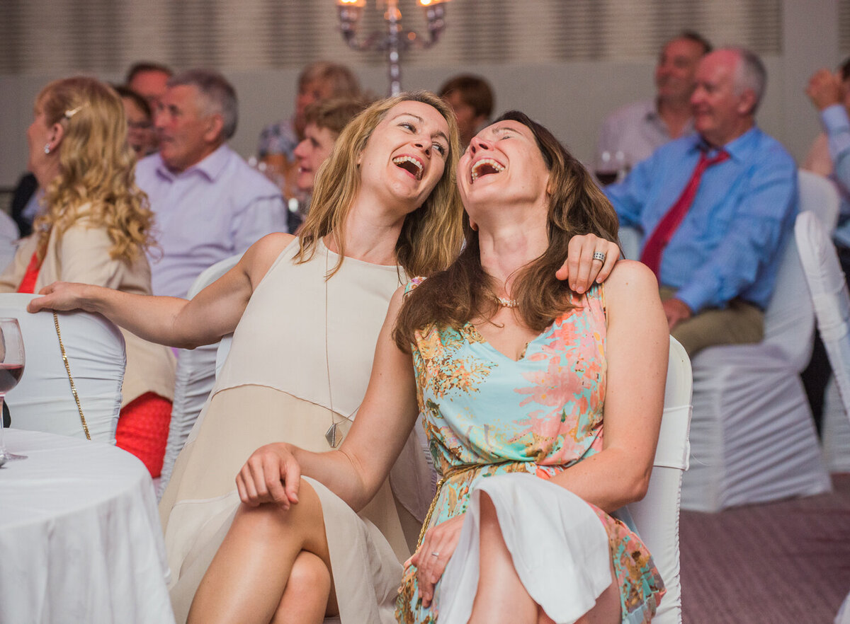Two female wedding guests laughing at wedding reception