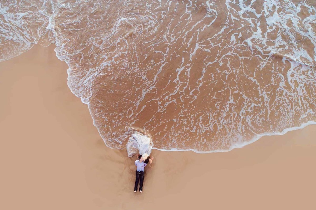 Husband and wife on Maui photographed by drone getting washed by waves