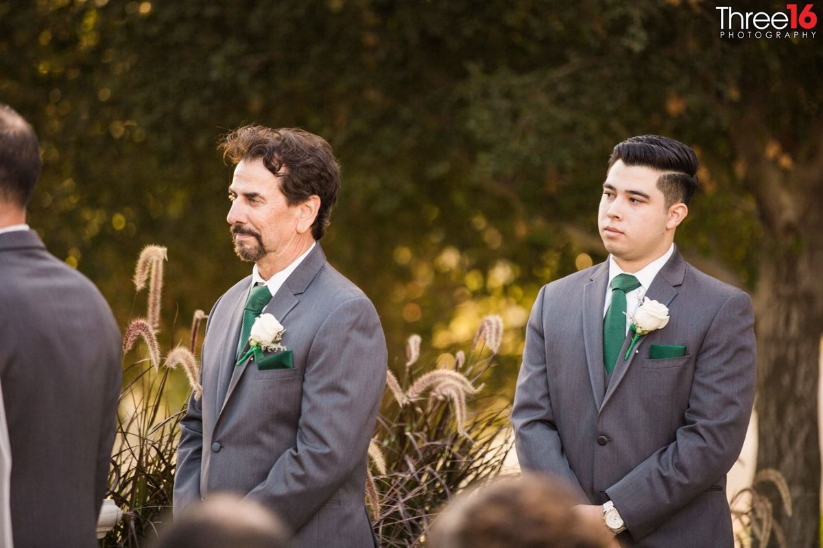 Groomsmen watch as the ceremony takes place