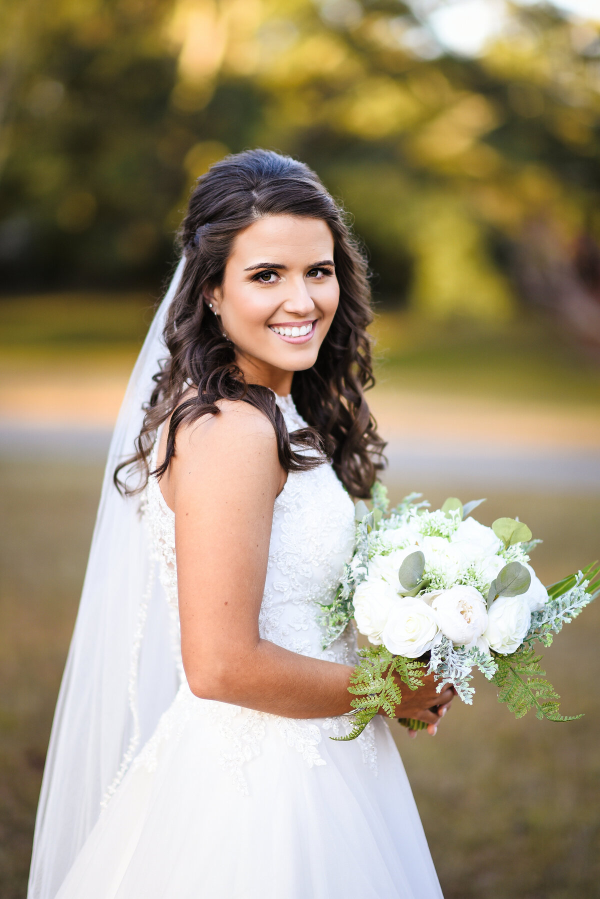 Beautiful bridal portrait photography: Bride turns to the camera outdoors in Mississippi
