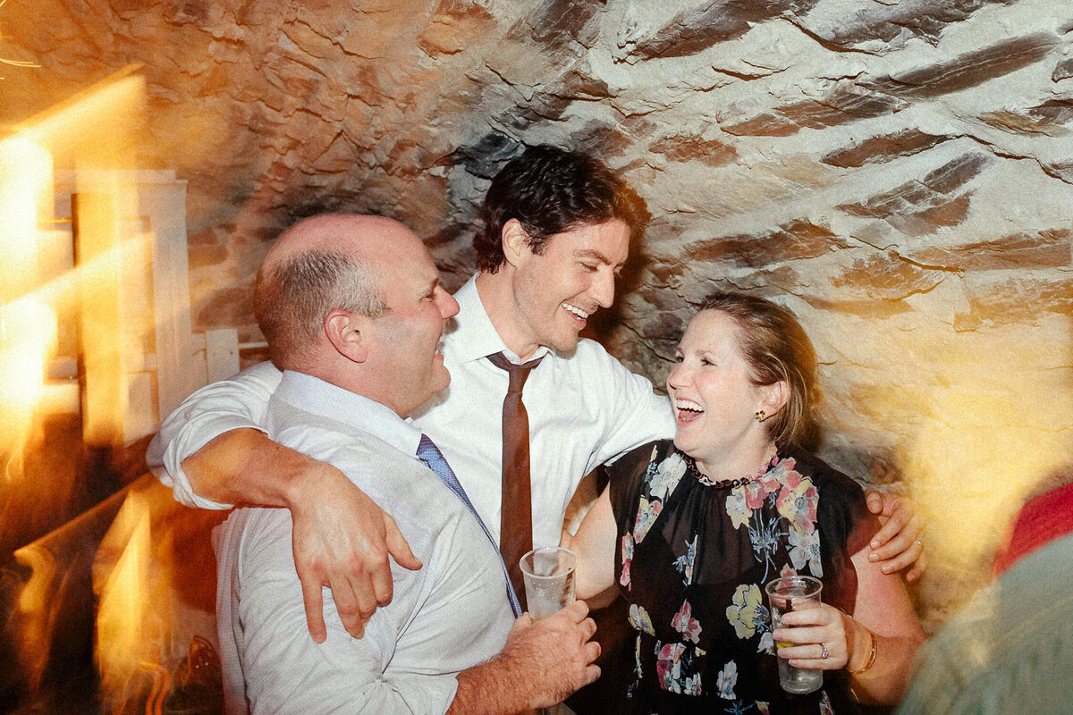 Man hugging couple in wine cellar during Italian Wedding