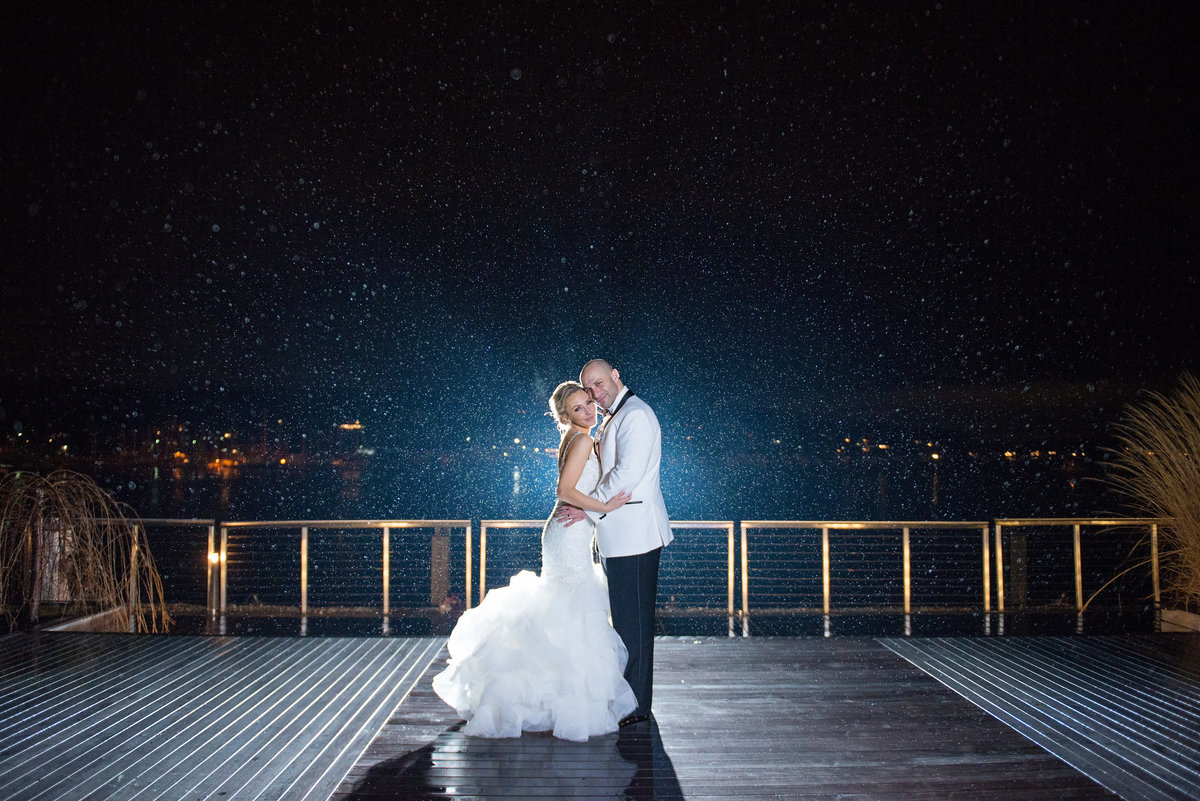 Bride and groom outside while it rains at Harbor Club at Prime