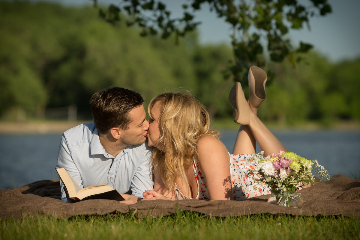 picnicking couple read poetry on the lake shore