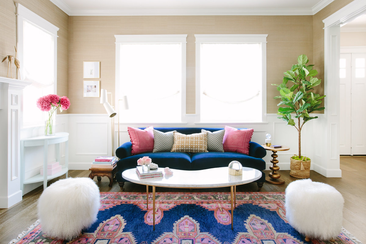 Navy and pink living room with navy velvet sofa, marble and gold coffee table, seagrass wallpaper, and caitlin Wilson Kismet  rug