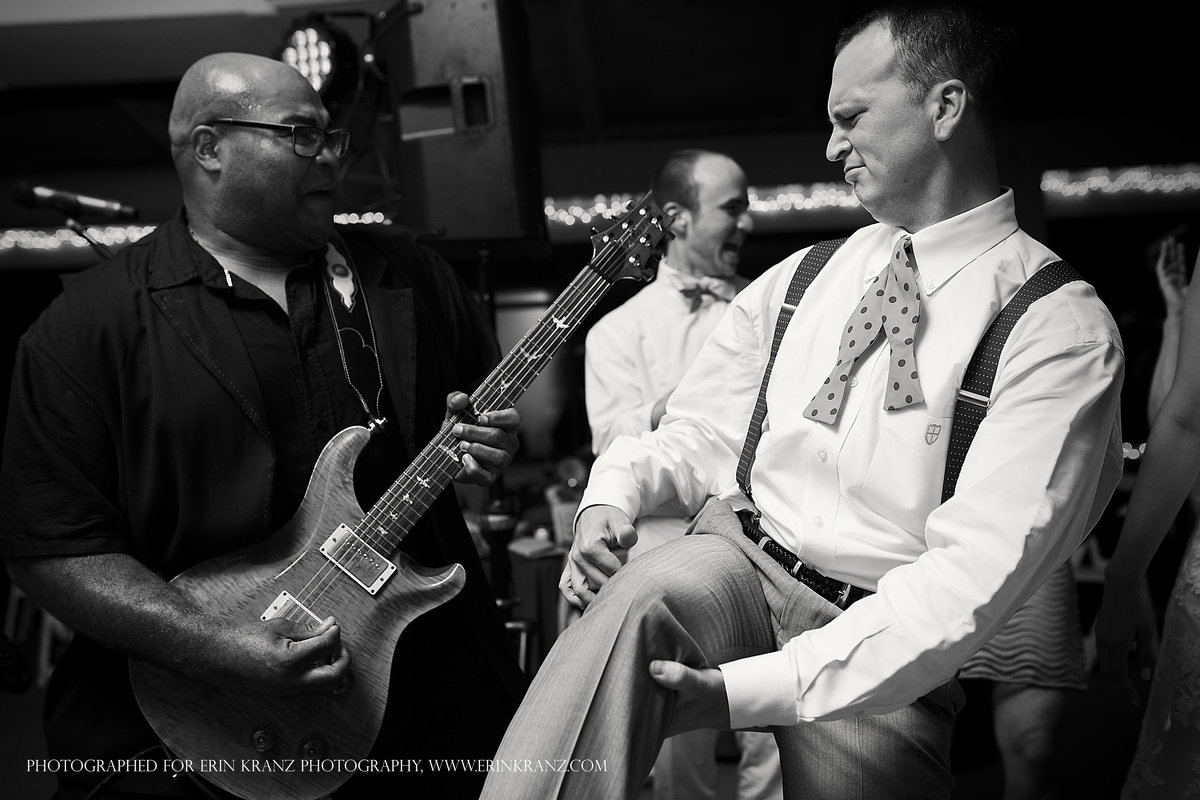 charlotte wedding photographer jamie lucido captures a fun reception detail of the groom dancing air guitar with the wedding band