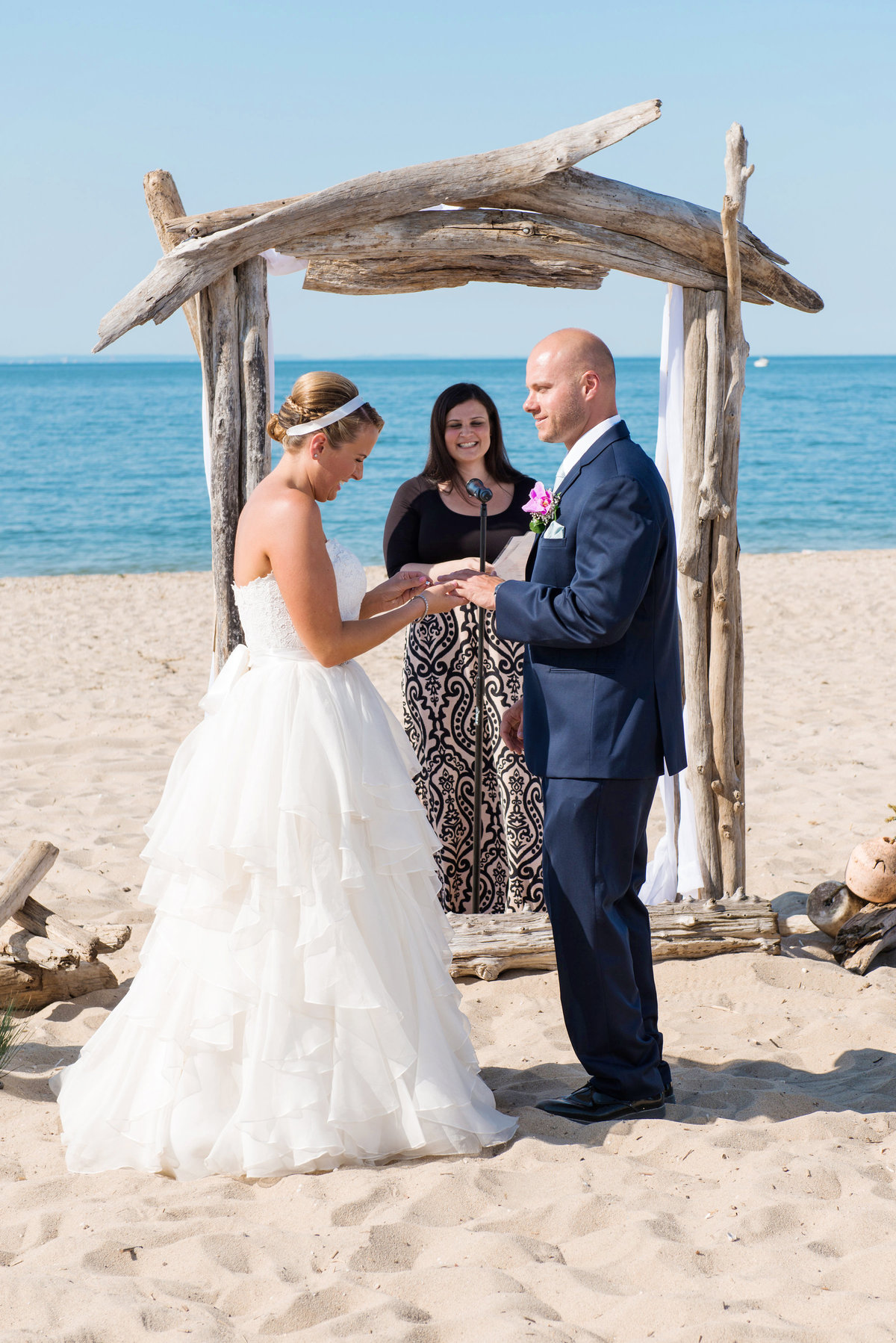 bride and groom ring exchange during wedding ceremony at Pavilion at Sunken Meadow